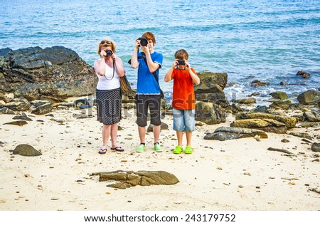 family takes a photo at the rocky beach with ocean in background - stock photo