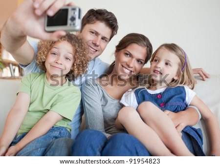 Family taking a photo of themselves in their living room - stock photo