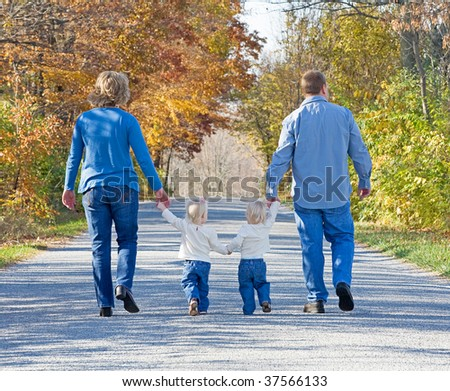 Family Taking a Walk in the Autumn - stock photo