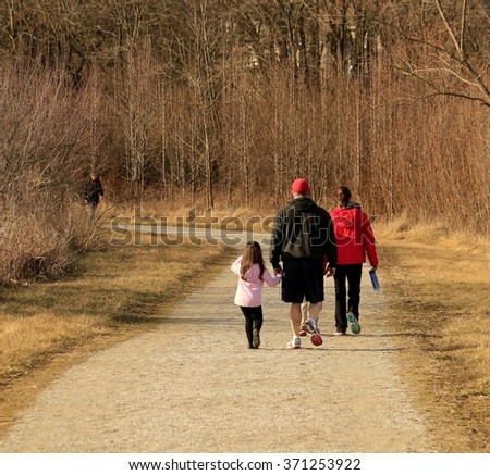 Family taking a walk on a warm winter day; Midwest - stock photo
