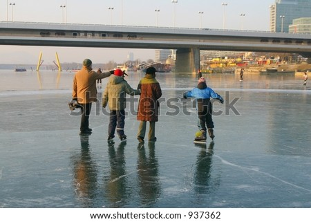 Family taking a walk on the frozen river danube - stock photo
