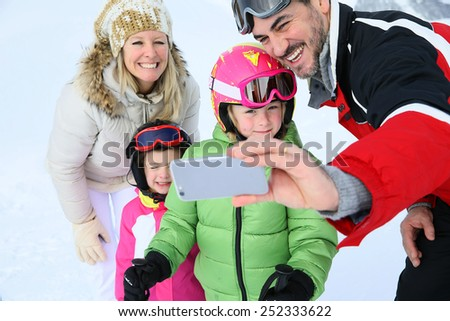 Family taking picture at the top of ski slope - stock photo