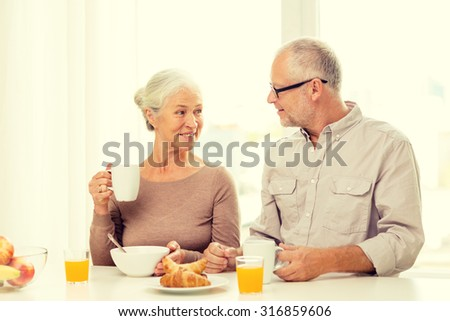 family, technology, food, drinks and people concept - happy senior couple having breakfast at home