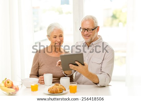 family, technology, food, drinks and people concept - happy senior couple with tablet pc computer having breakfast at home - stock photo