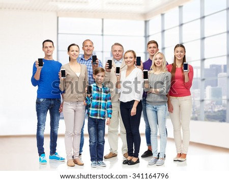 family, technology, generation and people concept - group of smiling men, women and boy with smartphones over empty office room or home - stock photo