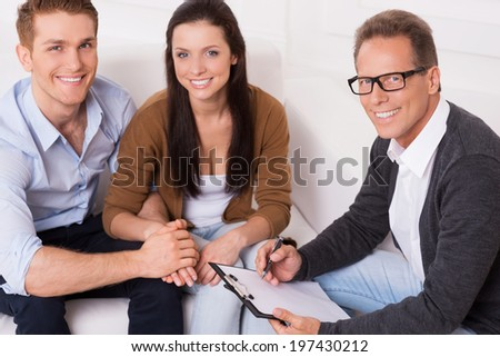 Family therapy . Top view of happy young couple and confident psychiatrist sitting together and smiling - stock photo