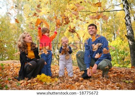 family throw autumnal leaves - stock photo