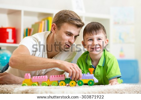 Family time. Cute kid boy joyfully playing building blocks with his father in nursery - stock photo