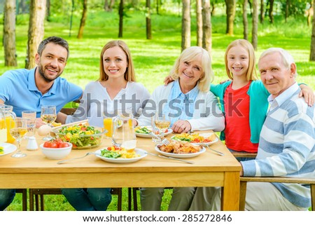 Family together. Happy family of five people bonding to each other and smiling while sitting at the dining table outdoors  - stock photo