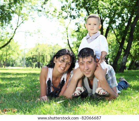 Family together in the summer park with a son - stock photo