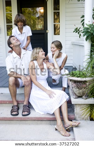 Family together on front porch step - stock photo