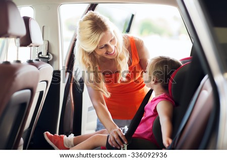 family, transport, safety, road trip and people concept - happy mother fastening child with car seat belt - stock photo