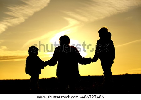 family travel - father and two kids walking at sunset