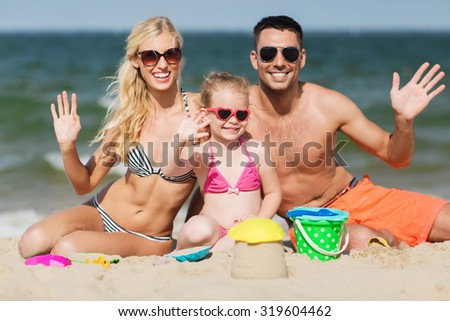 family, travel, vacation and people concept - happy man, woman and little girl in sunglasses with sand toys waving hands on summer beach - stock photo