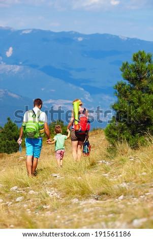 family traveling through the mountains - stock photo