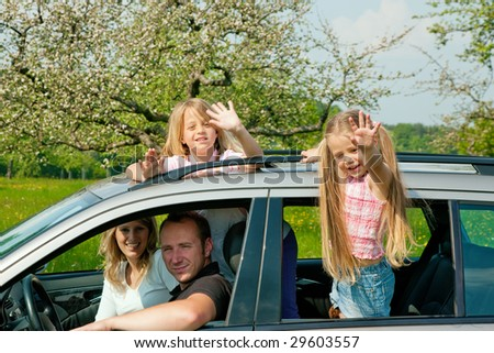 Family travelling by car, kids waving their hands - stock photo