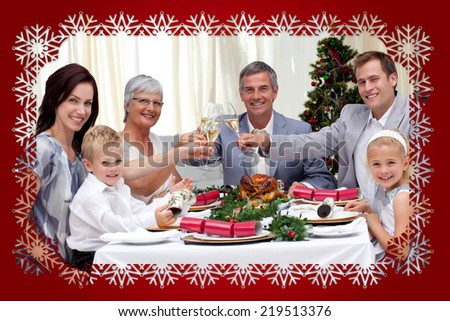 Family Tusting In A Christmas Dinner Against Snowflake Frame
