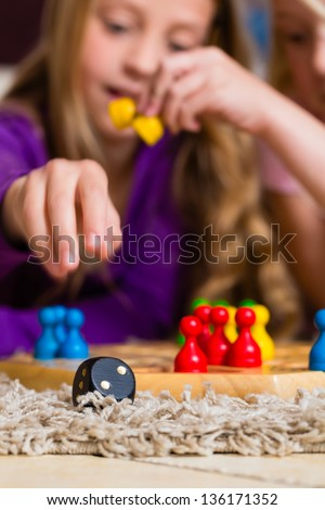 Family - two sisters - playing board game ludo at home on the floor, focus on dice in the front
