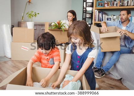 Family unpacking cardboard boxes at home - stock photo