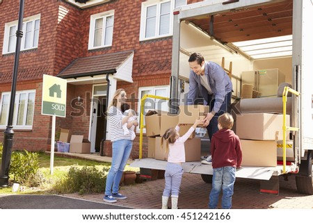 Family Unpacking Moving In Boxes From Removal Truck - stock photo