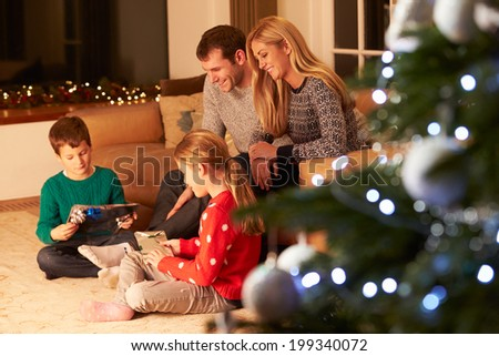 Family Unwrapping Gifts By Christmas Tree - stock photo