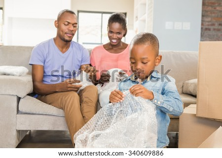 Family unwrapping things in new home in living room - stock photo