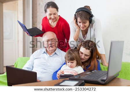 family uses few various electronic devices in home interior   - stock photo