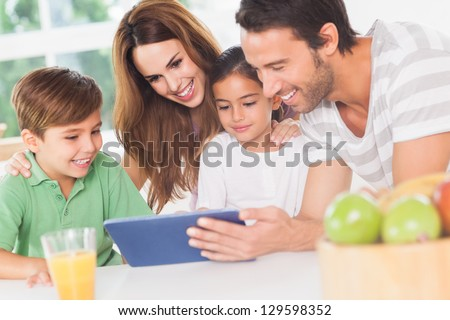 Family using a tablet pc in kitchen - stock photo