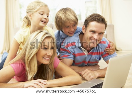 Family Using Laptop At Home Together - stock photo