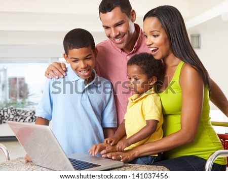 Family Using Laptop In Kitchen Together