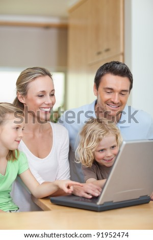 Family using laptop in the kitchen together - stock photo