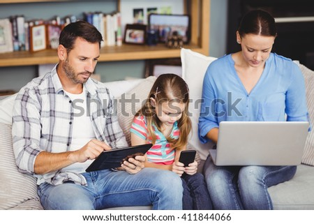 Family using modern technologies on sofa at home - stock photo