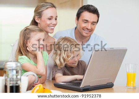 Family using the internet in the kitchen together - stock photo