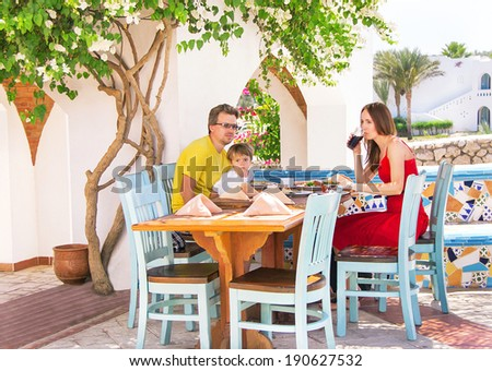 Family vacation. Caucasian happy family is sitting and having dinner at the summer restaurant. Relaxing family - mother, father and son. Close up, outdoor (Sharm El Sheikh, Egypt).  - stock photo