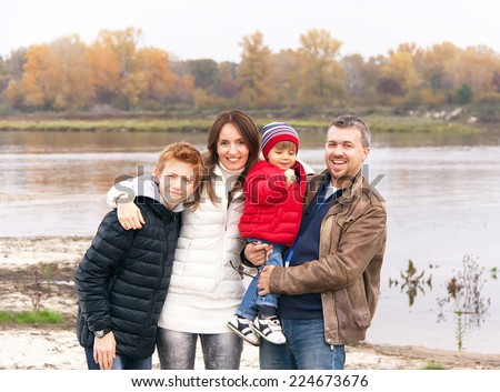 Family vacation. Caucasian happy family is standing and having fun by the river in the autumn day. Relaxing family on the autumnal beach - mother, father and two sons. Close up. - stock photo