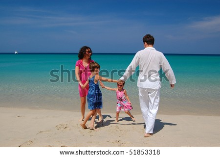 Family vacation. Parents playing with their kids on the beach - stock photo