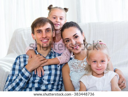 Family values: portrait of happy family with little girls indoors - stock photo