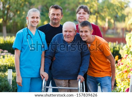 Family visiting grandfather at the nursing home, helping him with the walker. - stock photo