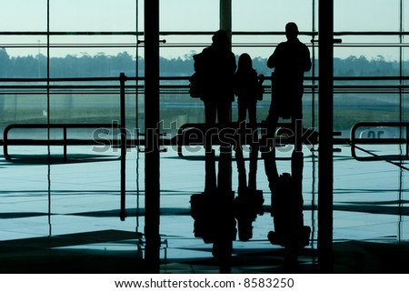 Family waiting at the international airport terminal - stock photo