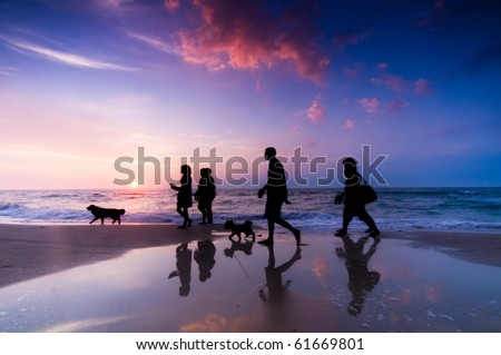 Family walk on the beach at sunset - stock photo
