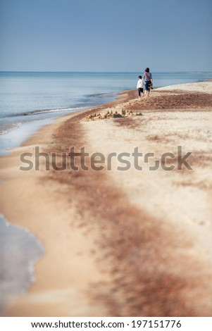 Family walking along a beach at Baltic sea on summer day - stock photo