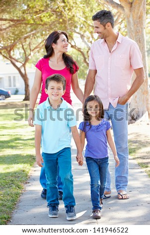 Family Walking Along Suburban Street - stock photo