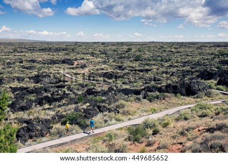 Family walking along the walkway through lava fields at Valley of  Fires Recreation Area,  Carrizozo, New Mexico - stock photo