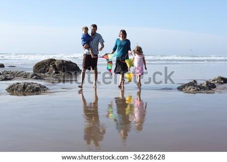 Family walking at beach - stock photo