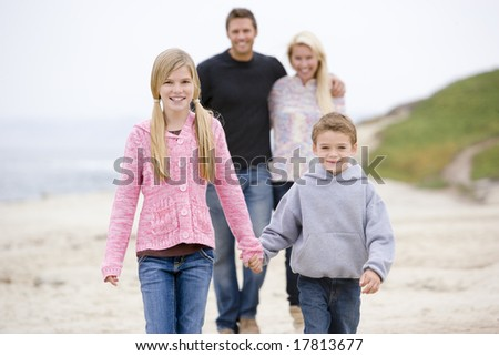 Family walking at beach holding hands smiling - stock photo