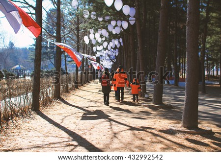 Family walking at park in winter.Family Walking Along winter Path. - stock photo
