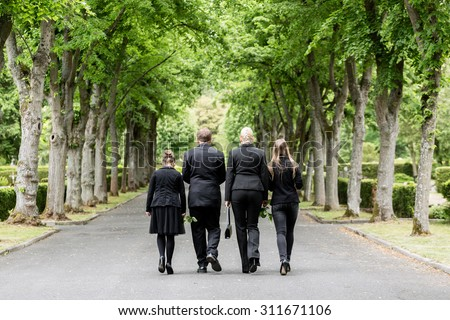 Family walking down alley at graveyard - stock photo