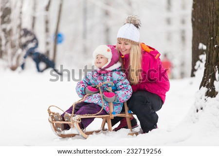 Family walking in a winter park. Child on sled - stock photo