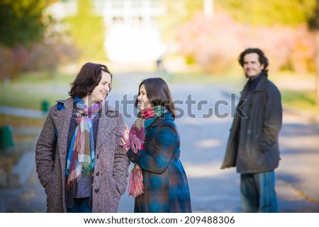 Family walking in an autumn park. Mother and her daughter talking and smiling. - stock photo
