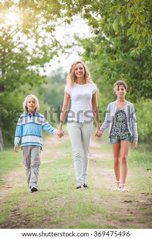 Family walking in the summer park - stock photo